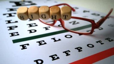 Dice spelling out sight falling onto eye test next to glasses — Stock Video