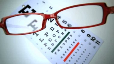 Red reading glasses falling on an eye test — Stock Video