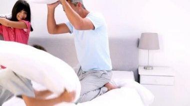 父亲和子女有一个枕头在床上打架 — 图库视频影像
