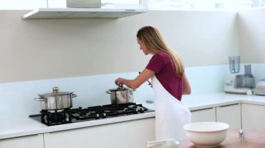 Blonde woman preparing meal in kitchen — Stock Video