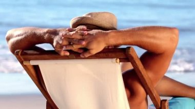 Handsome man with a straw hat relaxing on a deck chair — Stock Video