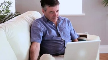 Mature man sitting on the couch using laptop and answering the phone — Stock Video