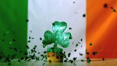 Shamrock confetti falling on st patricks day cupcake — Stock Video