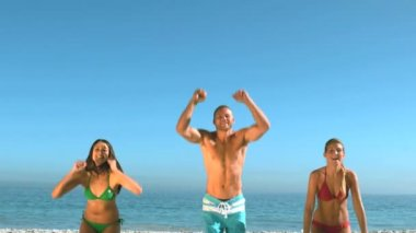 Attractive friends jumping on the beach at the same time — Stock Video