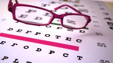 Pink reading glasses falling onto eye test — Stock Video