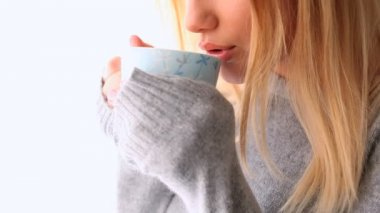 Attractive blonde in winter clothes holding mug of coffee — Stock Video