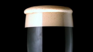 Foam head settling on pint of stout on black background — Stock Video
