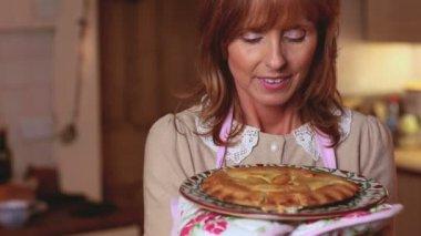 Femme mure sentant une tarte qu'elle a juste cuit — Vidéo