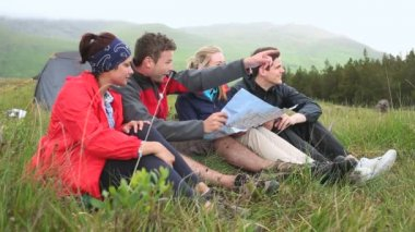 Friends on a camping trip laughing together and reading map — Stock Video