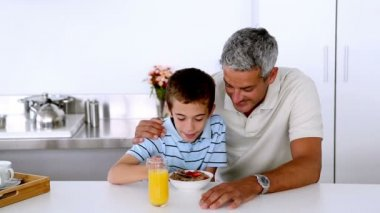 Father teasing son while he is having his breakfast — Stock Video