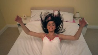 Charming young woman dropping back on her bed — Stock Video