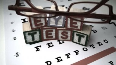 Red glasses falling onto eye test — Stock Video