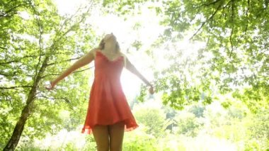 Beautiful teen twirling in the sunlight under the trees — Stock Video