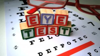 Red glasses falling next to blocks spelling out eye test — Stock Video