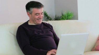 Glimlachende man met zijn laptop op de bank en de vrouw gaat zitten naast hem — Stockvideo