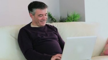 Smiling man using his laptop on the couch and wife sits down next to him — Vídeo de Stock