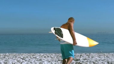 Handsome man with a surfboard running into the sea — Stock Video