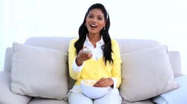 Woman sitting on sofa changing channel of television and eating popcorn — Stock Video