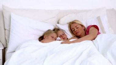 Mother sleeping peacefully with her twin girls — Stock Video