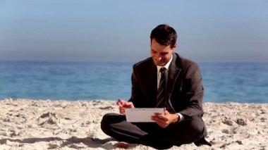 Uomo d'affari atono utilizzando tablet pc sulla spiaggia — Video Stock