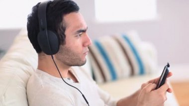 Handsome man with headphones listening to music on his smartphone — Stock Video
