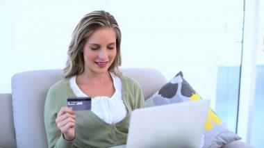 Zachwycony kobieta trzyma jej karty kredytowej i użyciu jej laptop — Wideo stockowe