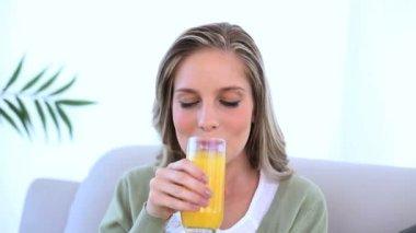 Beautiful woman drinking a glass of orange juice — Stock Video