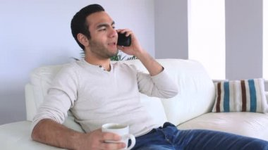 Handsome man answering the phone while relaxing on his sofa — Stock Video
