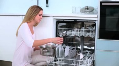 Bez uśmiechu blond kobieta umieścić jej naczynia w zmywarce w kuchni — Wideo stockowe