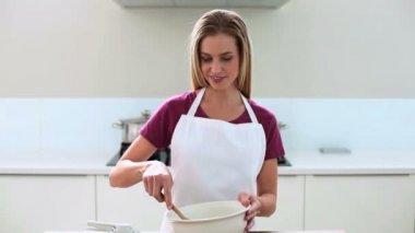 Smiling blonde woman preparing cake in kitchen — Stock Video