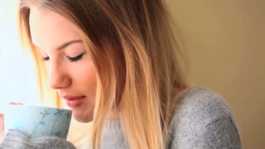 Attractive blonde wearing winter clothes drinking coffee — Stock Video