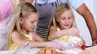 Tweelingzusjes gebak met hun ouders maken — Stockvideo