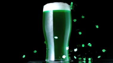 Shamrock confetti next to a pint of green beer — Stock Video