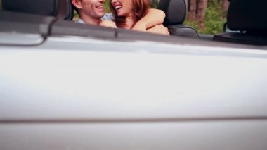 Young couple embracing in a convertible car — Stock Video