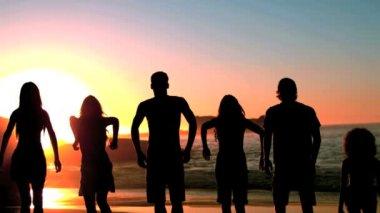 Grupo de amigos saltando en la playa bajo la oscuridad — Vídeo de stock