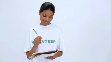 Smiling volunteer woman thinking and writting on notebook — Stockvideo