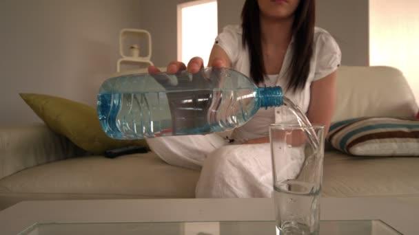 Mujer joven sentada en el sofá verter vidrio de agua — Vídeo de stock