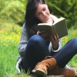 Woman sitting on grass reading a book — Stock Video