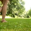 Beautiful teen walking away on the grass on a sunny day — Stock Video #31530691