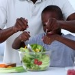 A father teaching to his son how to mix salad — Stock Video #31531057