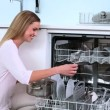 Blonde woman put her dishes in dishwasher and does a thumbs up in kitchen — Stock Video