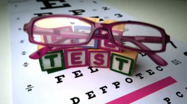 Pink glasses falling next to blocks spelling out eye test — Stock Video