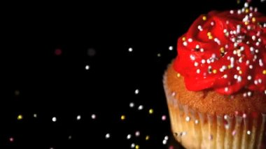 Sprinkles falling onto a cupcake — Stock Video