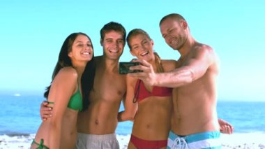 Group of friends taking self pictures on the beach — Stock Video