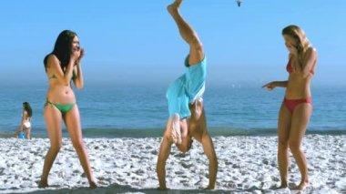 Man walking on hands between two pretty friends — Stock Video
