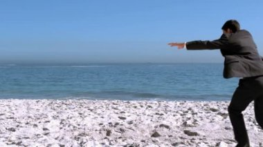 Businessman doing acrobatics on the beach — Stock Video