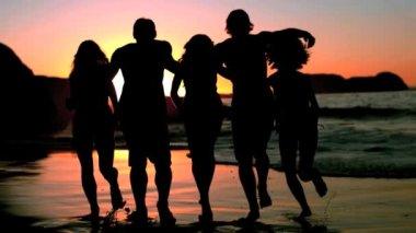 Amigos corriendo hacia el mar en el atardecer — Vídeo de stock