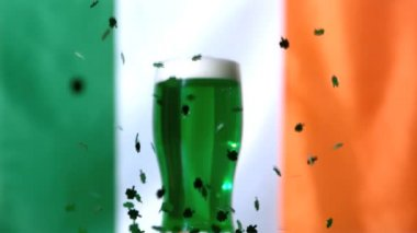 Shamrock confetti falling beside pint of green beer — Stock Video
