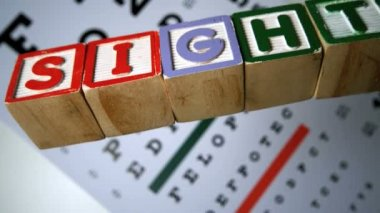 Blocks spelling out sight falling on eye test — 图库视频影像