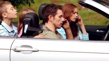 Parents on the phone in a convertible car — Stock Video #31530895